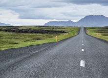 Empty road in Iceland. Simple road with a car at the back Royalty Free Stock Images