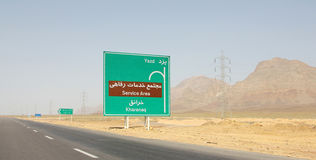 Empty road in the Iranian desert. With a direction road sign written in Farsi language Royalty Free Stock Photography