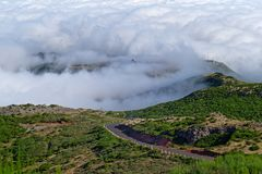 Empty road in the landscape against dense clouds. View from Pico do Arieiro on Portuguese island of Madeira stock photography