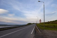 An empty road with lanterns on the shore of the great Volga river. stock photos
