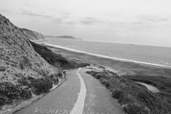 Empty road leading down on azkorri beach in black and white, basque country, spain Stock Photography
