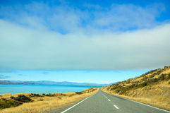 Empty road leading through scenic countryside, New Zealand. New Zealand is a country in the southwestern Pacific Ocean consisting of 2 main islands, both marked Royalty Free Stock Photo