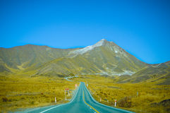 Empty road leading through scenic countryside, New Zealand. New Zealand is a country in the southwestern Pacific Ocean consisting of 2 main islands, both marked Royalty Free Stock Photography