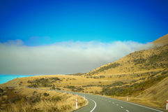 Empty road leading through scenic countryside, New Zealand. Zealand is a country of stunning and diverse natural beauty: jagged mountains, rolling pasture land Royalty Free Stock Photography