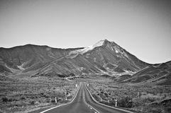Empty road leading through scenic countryside, New Zealand. Zealand is a country of stunning and diverse natural beauty: jagged mountains, rolling pasture land Stock Photos