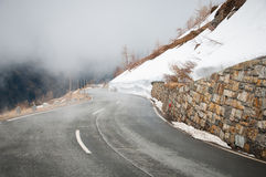 Empty road leading through scenic countryside, Snow & fog at Grossglockner mountain, Austria Stock Photos