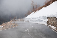 Empty road leading through scenic countryside, Snow & fog at Grossglockner mountain, Austria Stock Images