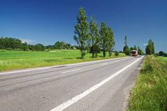 Empty road lined with poplar alley in the countryside, in the distance passing red truck Royalty Free Stock Images