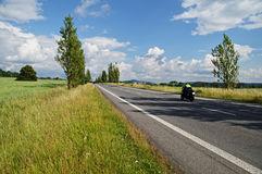 An empty road lined with poplar alley in the countryside, passing motorcycle Royalty Free Stock Image