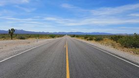 Empty road in the middle of desert. Empty road in the middle of desert with blue sky and white clouds Stock Photos