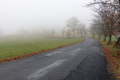 Empty road in misty day Royalty Free Stock Images