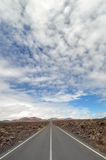 Empty road through the Montanas del Fuego. Empty road through the lava fields on Lanzarote, Canary Islands, Spain Royalty Free Stock Photography