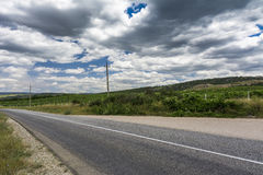 Empty road through a mountain valley. Beautiful cloudy sky. Royalty Free Stock Photo