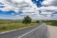 Empty road through a mountain valley. Beautiful cloudy sky. Royalty Free Stock Photos