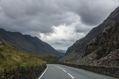 Empty road through mountains. With cloudy weather Stock Image