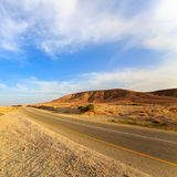 Empty road in a mountains in desert at sunset. Empty road in a mountains in desert Negev at sunset Royalty Free Stock Image