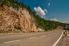 Road in the mountains of Montenegro. An empty road in the mountains of Montenegro on a sunny day Stock Image