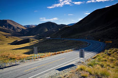 Empty road through mountains in New Zealand. Empty winding road through mountains in New Zealand on a sunny summer morning Stock Photos