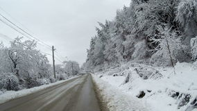 Empty road in the mountains during winter with snow covered trees on the side. View of an empty road in the mountains during winter with snow covered trees on stock footage