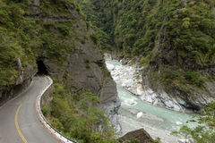 Empty road at a rugged, rocky and lush landscape at Taroko. Empty road and river at a rugged, rocky, lush and mountainous landscape at the Taroko National Park Stock Photos