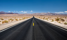 Empty road running through Death Valley National Park stock photos
