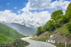 Empty road serpentine in the mountains, blue sky with clouds, mountain peaks in the snow and green hills background stock photo