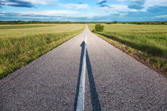Empty road with a shadow in the shape of arrow Royalty Free Stock Images