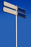 Empty road sign on a high pole. Two directions, isolated against a clear blue sky Royalty Free Stock Image