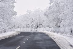 Empty road with snow covered landscape. Beautiful winter seasonal background for transport and cars. Royalty Free Stock Images