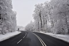 Empty road with snow covered landscape. Beautiful winter seasonal background for transport and cars. Stock Photos