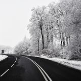 Empty road with snow covered landscape. Beautiful winter seasonal background for transport and cars. Stock Photo