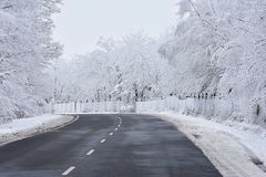 Empty road with snow covered landscape. Beautiful winter seasonal background for transport and cars. Stock Images