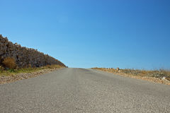 Empty Road with Stone Fence. And Blue Sky Above Stock Photos