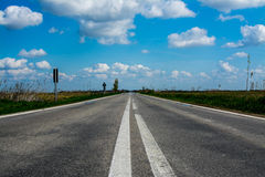 Empty Road. On a sunny day with bright blue sky and beautiful white clouds Stock Image