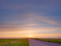Empty road on sunrise. Bright sunrise over countryside empty road Royalty Free Stock Image