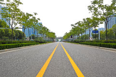 Empty road surface with modern city buildings background. Empty straight line road surface with modern city buildings background Stock Photos
