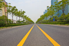 Empty road surface with modern city buildings background. Empty straight line road surface with modern city buildings background Royalty Free Stock Images