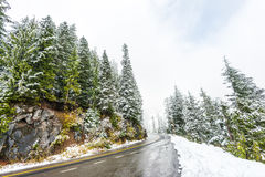 Empty road to the mountain with snow covered landscape in winter Stock Photos