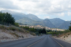 Empty road to a town in mountains. Empty road to  town in mountains Royalty Free Stock Photography