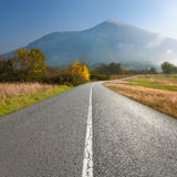 Empty road towards the mountain peak at morning Stock Images