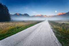 Empty road towards the mountain peaks at dawn Royalty Free Stock Photography