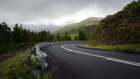 Mountain road turning to the right at the Azores Portugal. Mountain Road turn bending downhill to the right in a beautiful landscape  - Azores, Sao Miguel Island Stock Images