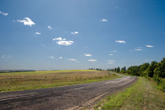 Empty road with a view of agricultural fields. And clouds in sky Stock Image