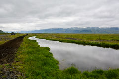 Empty road with view to mountain with small river along the way Stock Photography