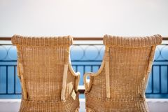 Empty Romantic Beach Chairs against sea. Two natural wood beach chairs facing a still horizon Stock Image