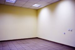 Empty room. Corner of empty office room with floor of stones, ceiling, lamps and yellow walls Stock Image