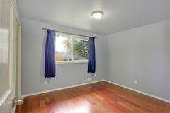 Empty room with blue walls paint color. Small window dressed in blue curtains and hardwood floor royalty free stock photography
