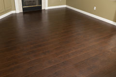 Empty Room with Brown Laminate Flooring. Beautiful Newly Installed Brown Laminate Flooring and Baseboards in Home stock images