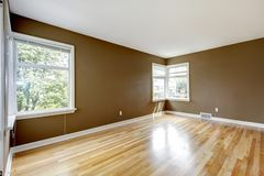 Empty room with brown walls and hardwood floor. Stock Photos