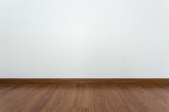Empty room with brown wood laminate floor and white mortar wall stock photos